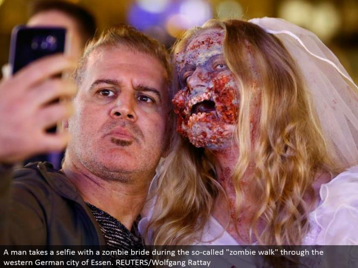 """A man brings a selfie with a zombie lady of the hour amid the alleged """"zombie stroll"""" through the western German city of Essen. REUTERS/Wolfgang Rattay"""