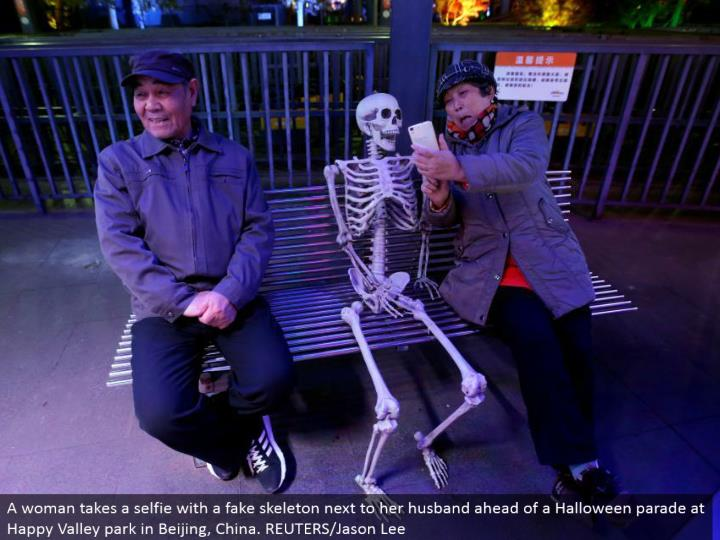 A lady brings a selfie with a fake skeleton beside her significant other in front of a Halloween parade at Happy Valley stop in Beijing, China. REUTERS/Jason Lee
