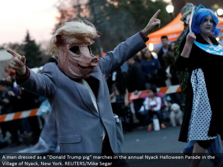 """A man dressed as a """"Donald Trump pig"""" walks in the yearly Nyack Halloween Parade in the Village of Nyack, New York. REUTERS/Mike Segar"""