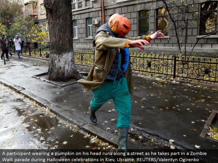 A member wearing a pumpkin on his head keeps running along a road as he participates in a Zombie Walk parade amid Halloween festivities in Kiev, Ukraine. REUTERS/Valentyn Ogirenko