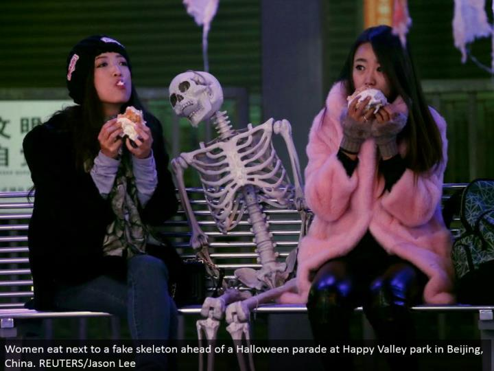 Women eat alongside a fake skeleton in front of a Halloween parade at Happy Valley stop in Beijing, China. REUTERS/Jason Lee