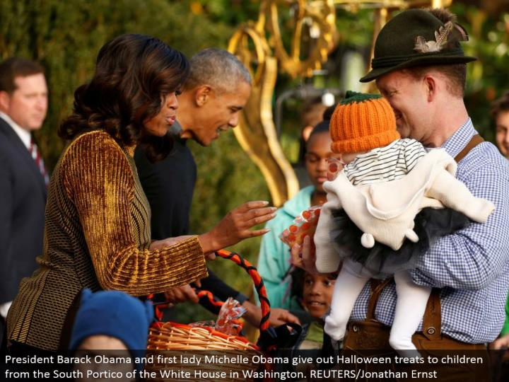 President Barack Obama and first woman Michelle Obama give out Halloween treats to youngsters from the South Portico of the White House in Washington. REUTERS/Jonathan Ernst