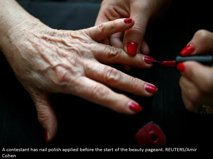 A hopeful has nail clean connected before the begin of the magnificence show. REUTERS/Amir Cohen