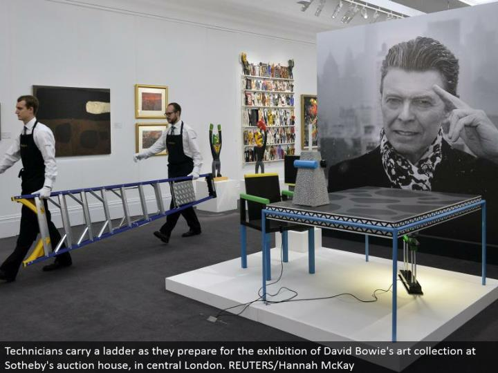 Technicians convey a stepping stool as they plan for the presentation of David Bowie's craft gathering at Sotheby's sale house, in focal London. REUTERS/Hannah McKay