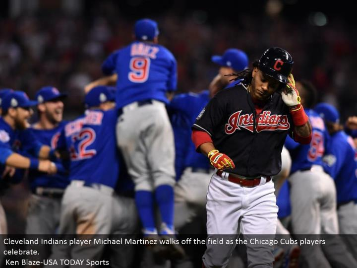 Cleveland Indians player Michael Martinez strolls off the field as the Chicago Cubs players celebrate.  Ken Blaze-USA TODAY Sports