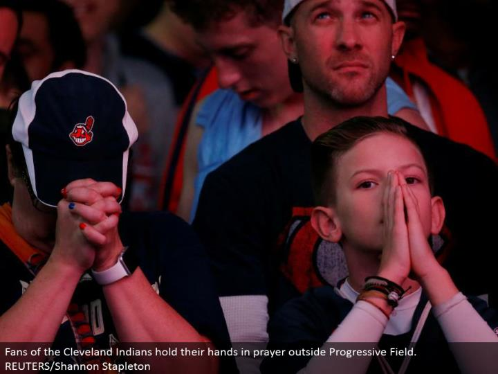 Fans of the Cleveland Indians hold their hands in supplication outside Progressive Field. REUTERS/Shannon Stapleton