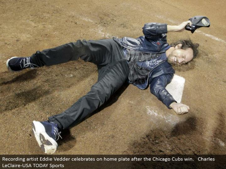 Recording craftsman Eddie Vedder celebrates on home plate after the Chicago Cubs win. Charles LeClaire-USA TODAY Sports