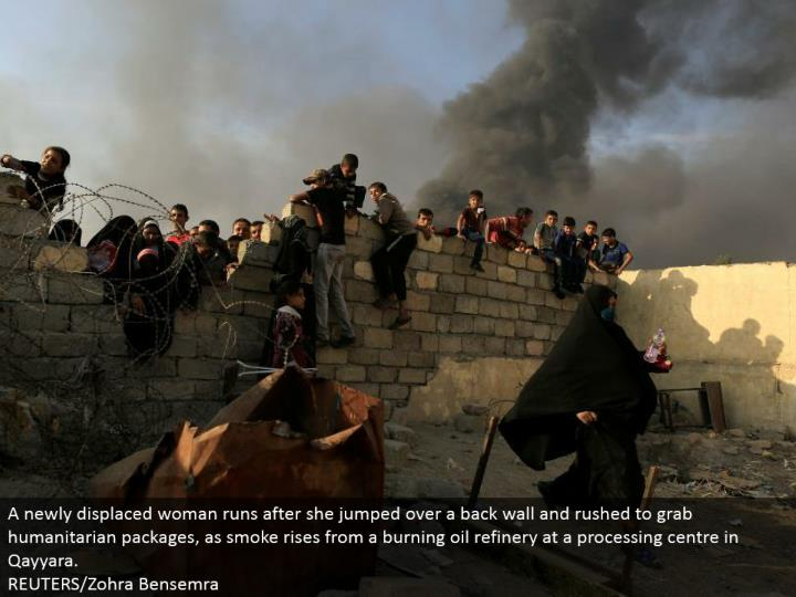 A recently dislodged lady pursues she bounced over a back divider and raced to snatch philanthropic bundles, as smoke ascends from a smoldering oil refinery at a handling focus in Qayyara.  REUTERS/Zohra Bensemra