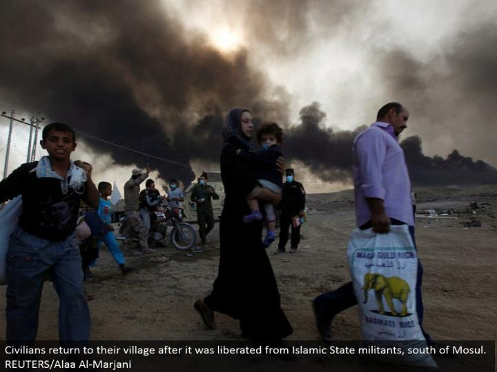Civilians come back to their town after it was freed from Islamic State aggressors, south of Mosul.  REUTERS/Alaa Al-Marjani