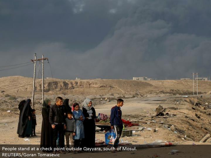 People remain at a check point outside Qayyara, south of Mosul.  REUTERS/Goran Tomasevic