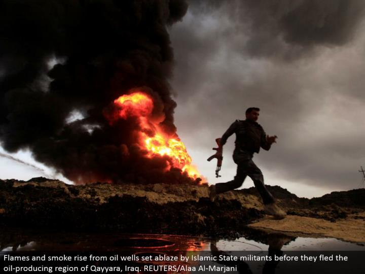 Flames and smoke ascend from oil wells set on fire by Islamic State aggressors before they fled the oil-creating area of Qayyara, Iraq. REUTERS/Alaa Al-Marjani