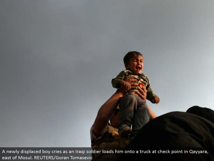 A recently dislodged kid cries as an Iraqi officer loads him onto a truck at check point in Qayyara, east of Mosul. REUTERS/Goran Tomasevic