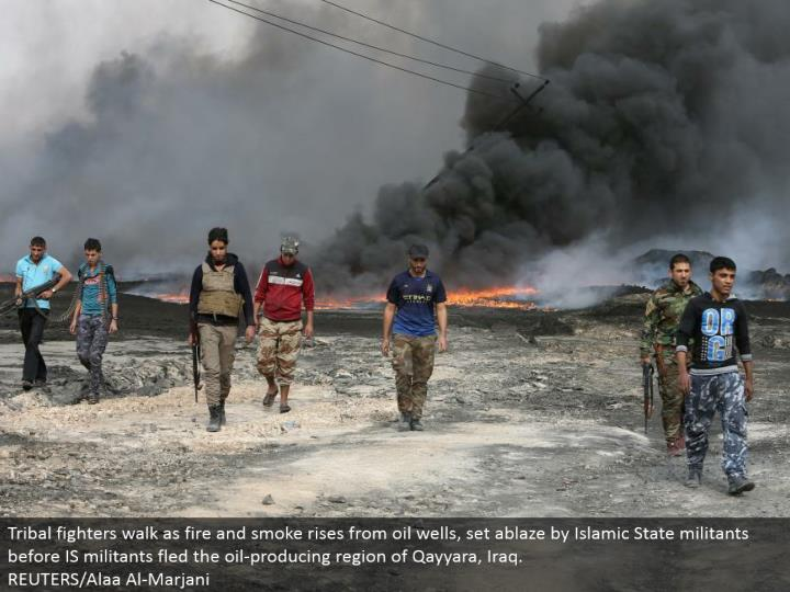Tribal warriors stroll as flame and smoke ascends from oil wells, set on fire by Islamic State activ...