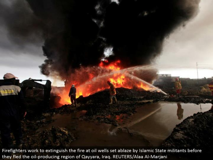 Firefighters work to quench the fire at oil wells set on fire by Islamic State aggressors before they fled the oil-delivering area of Qayyara, Iraq. REUTERS/Alaa Al-Marjani