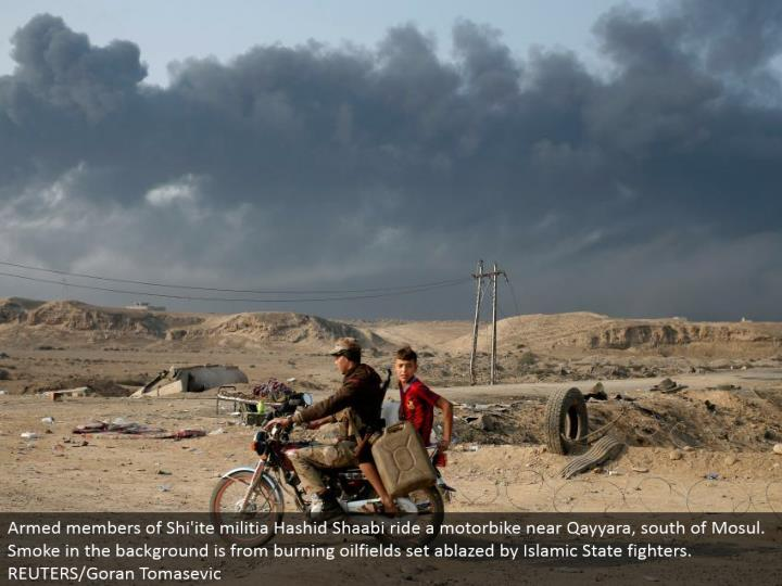 Armed individuals from Shi'ite civilian army Hashid Shaabi ride a motorbike close Qayyara, south of Mosul. Smoke out of sight is from blazing oilfields set ablazed by Islamic State warriors.  REUTERS/Goran Tomasevic