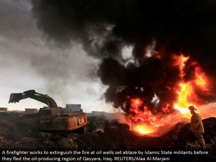 A firefighter attempts to stifle the fire at oil wells set on fire by Islamic State aggressors before they fled the oil-delivering locale of Qayyara, Iraq. REUTERS/Alaa Al-Marjani