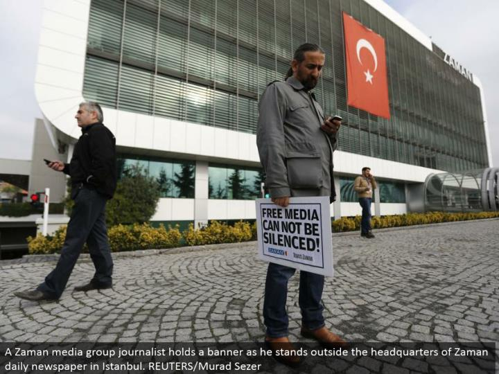 A Zaman media bunch columnist holds a pennant as he stands outside the central command of Zaman every day daily paper in Istanbul. REUTERS/Murad Sezer