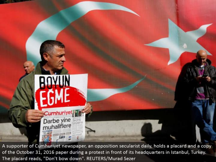 """A supporter of Cumhuriyet daily paper, a restriction secularist day by day, holds a notice and a duplicate of the October 31, 2016 paper amid a challenge before its home office in Istanbul, Turkey. The notice peruses, """"Don't bow down"""". REUTERS/Murad Sezer"""