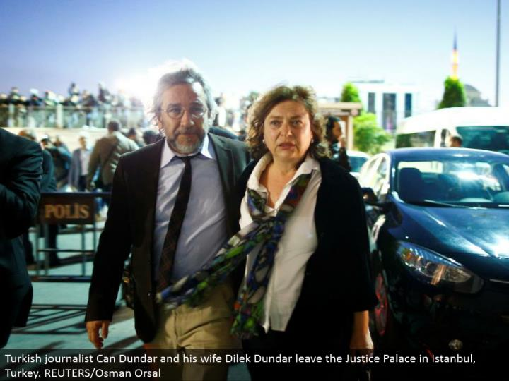 Turkish writer Can Dundar and his significant other Dilek Dundar leave the Justice Palace in Istanbul, Turkey. REUTERS/Osman Orsal