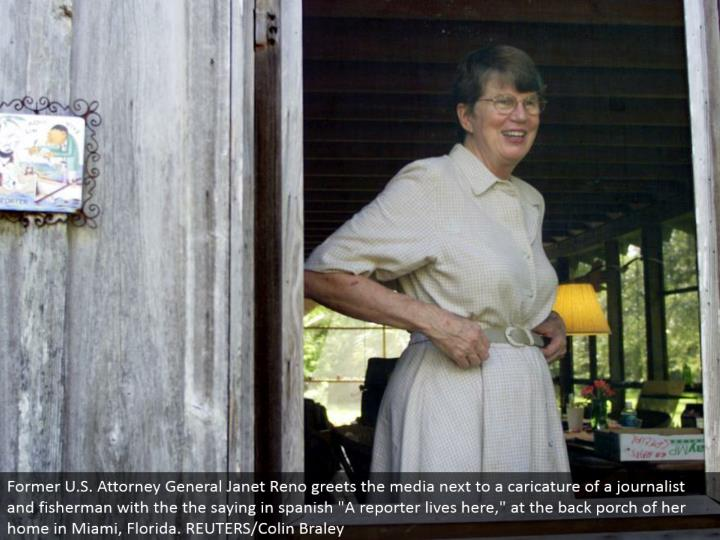 "Former U.S. Lawyer General Janet Reno welcomes the media alongside a personification of a columnist and angler with the maxim in spanish ""A journalist lives here,"" at the back patio of her home in Miami, Florida. REUTERS/Colin Braley"