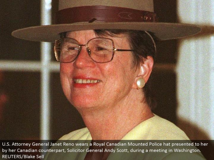 U.S. Lawyer General Janet Reno wears a Royal Canadian Mounted Police cap introduced to her by her Canadian partner, Solicitor General Andy Scott, amid a meeting in Washington. REUTERS/Blake Sell