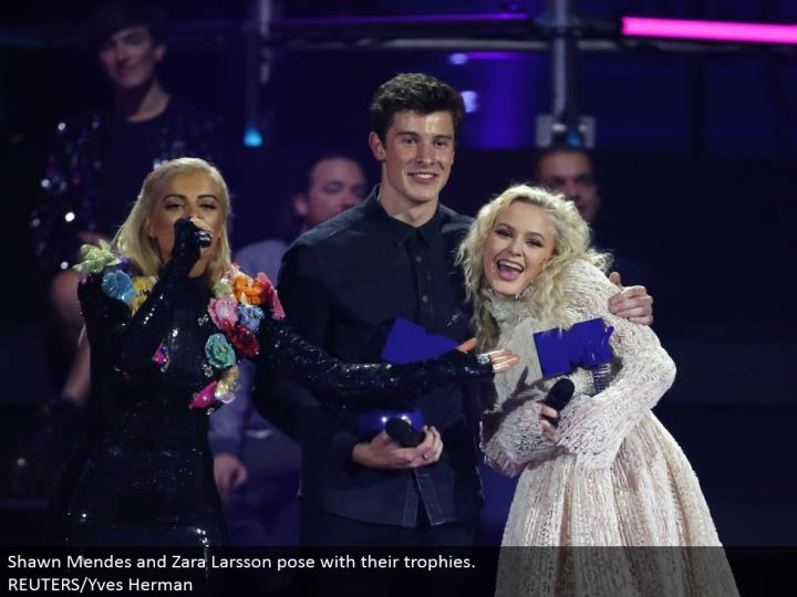 Shawn Mendes and Zara Larsson posture with their trophies.  REUTERS/Yves Herman