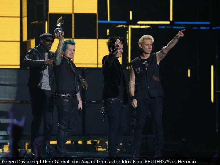 Green Day acknowledge their Global Icon Award from on-screen character Idris Elba. REUTERS/Yves Herman