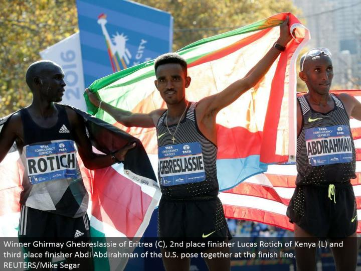 Winner Ghirmay Ghebreslassie of Eritrea (C), second place finisher Lucas Rotich of Kenya (L) and third place finisher Abdi Abdirahman of the U.S. posture together toward the complete line.  REUTERS/Mike Segar
