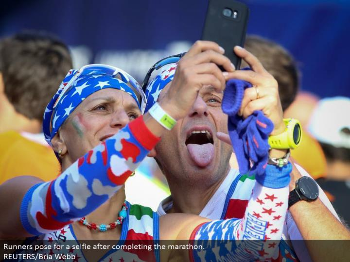 Runners posture for a selfie in the wake of finishing the marathon.  REUTERS/Bria Webb