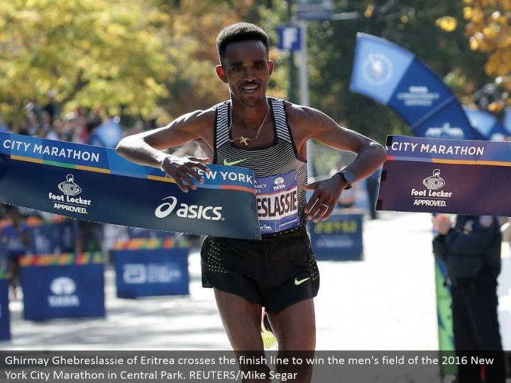 Ghirmay Ghebreslassie of Eritrea crosses the complete line to win the men's field of the 2016 New York City Marathon in Central Park. REUTERS/Mike Segar