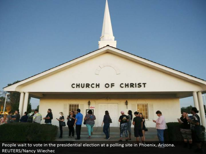 People hold up to vote in the presidential race at a surveying site in Phoenix, Arizona. REUTERS/Nan...