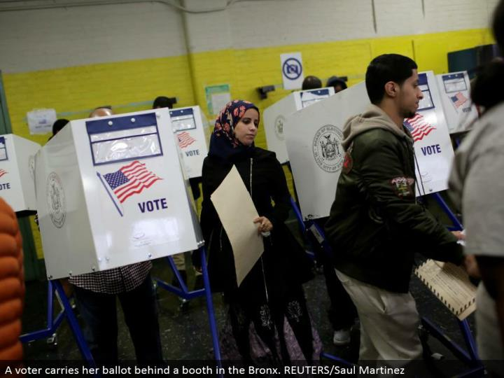 A voter conveys her ticket behind a stall in the Bronx. REUTERS/Saul Martinez
