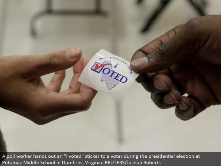 "A survey laborer distributes an ""I voted"" sticker to a voter amid the presidential decision at Potomac Middle School in Dumfries, Virginia. REUTERS/Joshua Roberts"