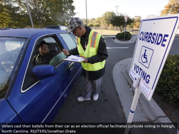 Voters cast their votes from their auto as a race official encourages curbside voting in Raleigh, North Carolina. REUTERS/Jonathan Drake