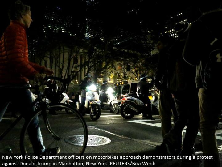 New York Police Department officers on motorbikes approach demonstrators amid a challenge against Donald Trump in Manhattan, New York. REUTERS/Bria Webb