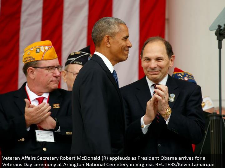 Veteran Affairs Secretary Robert McDonald (R) extols as President Obama lands for a Veterans Day function at Arlington National Cemetery in Virginia. REUTERS/Kevin Lamarque
