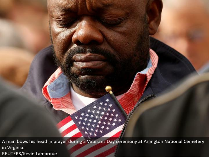 A man bows his head in petition amid a Veterans Day function at Arlington National Cemetery in Virgi...