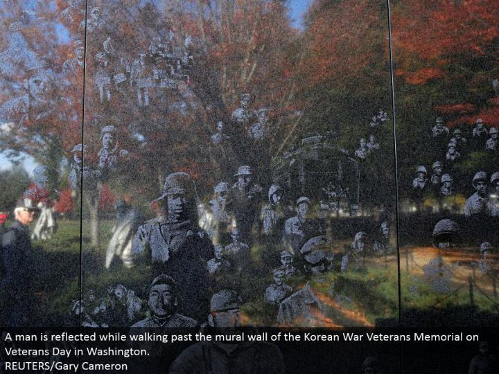 A man is reflected while strolling past the painting mass of the Korean War Veterans Memorial on Veterans Day in Washington.  REUTERS/Gary Cameron