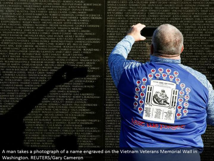A man takes a photo of a name engraved on the Vietnam Veterans Memorial Wall in Washington. REUTERS/Gary Cameron