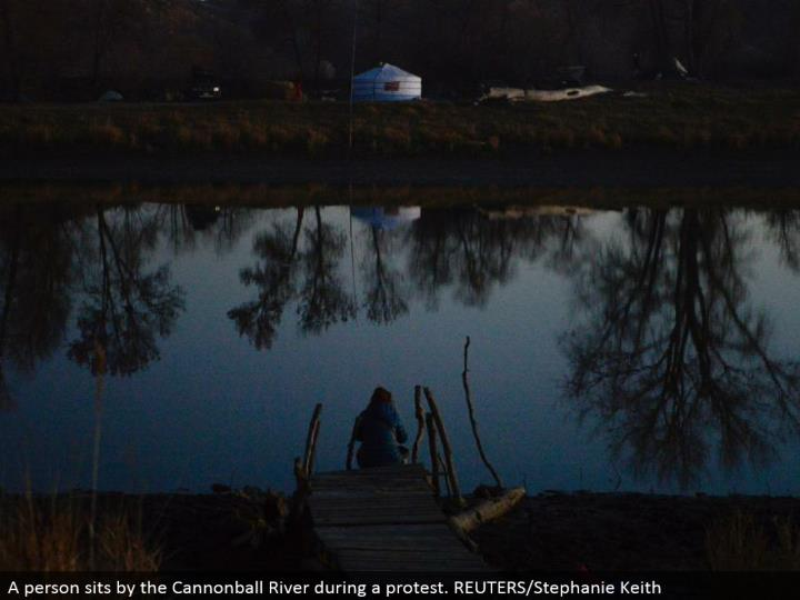 A individual sits by the Cannonball River amid a dissent. REUTERS/Stephanie Keith