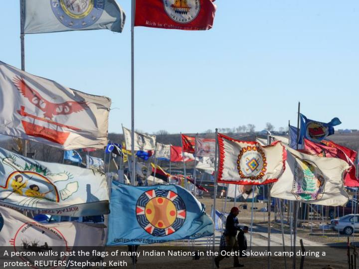 A individual strolls past the banners of numerous Indian Nations in the Oceti Sakowin camp amid a challenge. REUTERS/Stephanie Keith