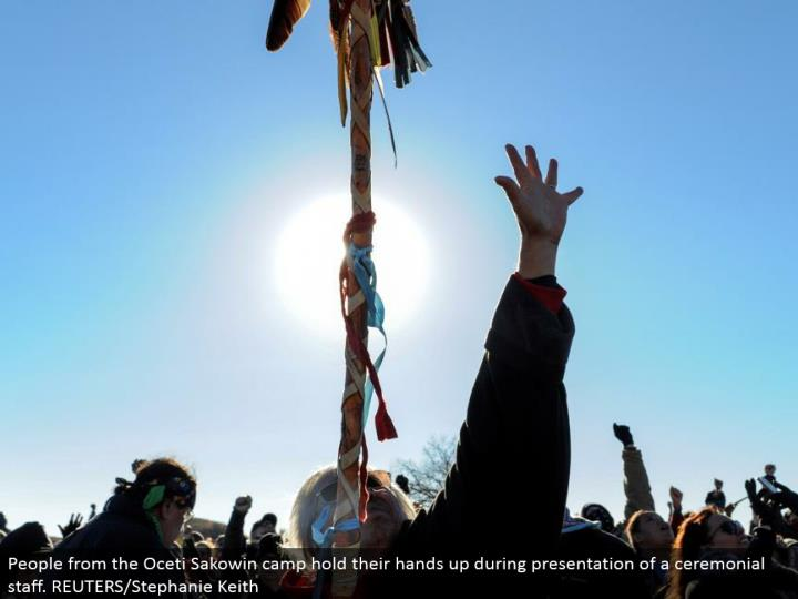 People from the Oceti Sakowin camp hold their hands up amid presentation of a stately staff. REUTERS/Stephanie Keith