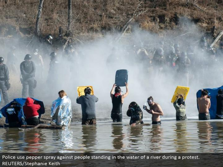 Police utilize pepper splash against individuals remaining in the water of a waterway amid a challenge. REUTERS/Stephanie Keith