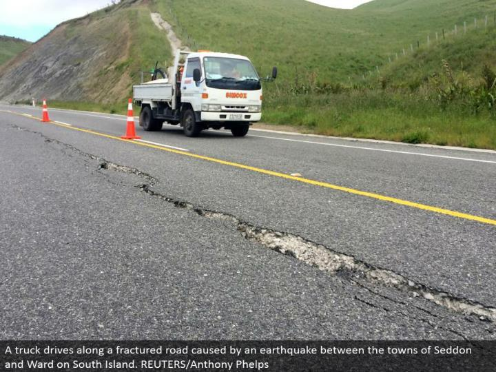 A truck drives along a cracked street brought on by a quake between the towns of Seddon and Ward on South Island. REUTERS/Anthony Phelps