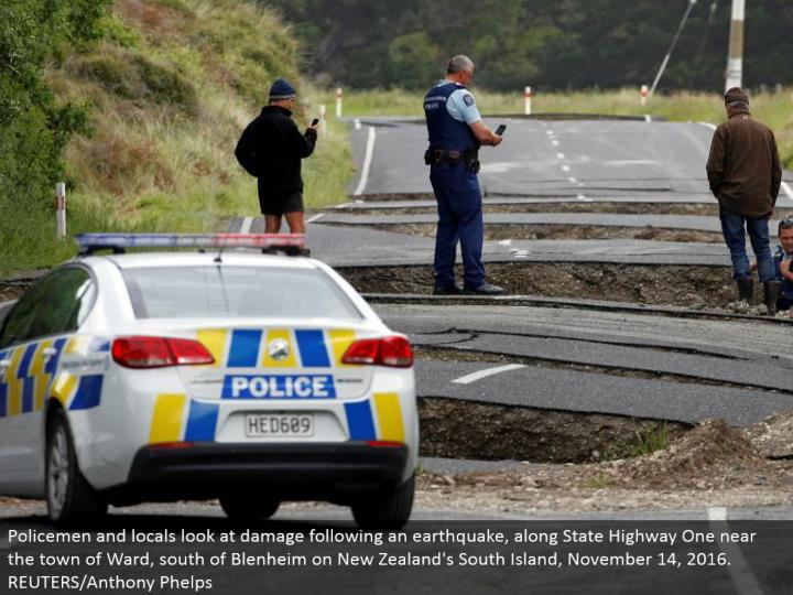Policemen and local people take a gander at harm taking after a quake, along State Highway One close...