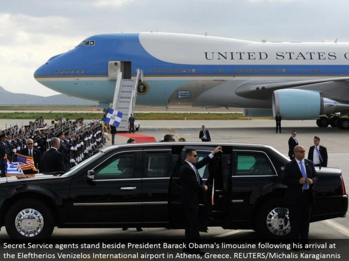 Secret Service specialists remain alongside President Barack Obama's limousine taking after his land...