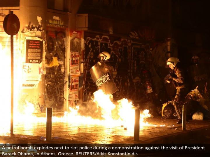 A petrol bomb detonates beside mob police amid a show against the visit of President Barack Obama, in Athens, Greece. REUTERS/Alkis Konstantinidis