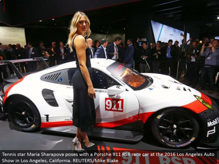 Tennis star Maria Sharapova postures with a Porsche 911 RSR race auto at the 2016 Los Angeles Auto Show in Los Angeles, California. REUTERS/Mike Blake