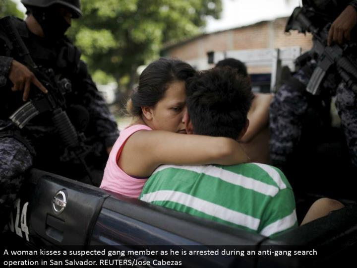 A lady kisses a speculated posse part as he is captured amid a hostile to pack seek operation in San Salvador. REUTERS/Jose Cabezas