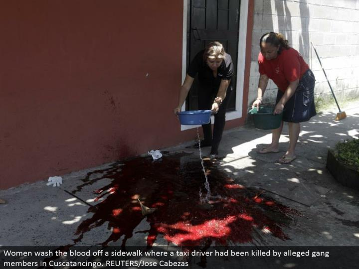 Women wash the blood off a walkway where a cab driver had been slaughtered by claimed group individuals in Cuscatancingo. REUTERS/Jose Cabezas